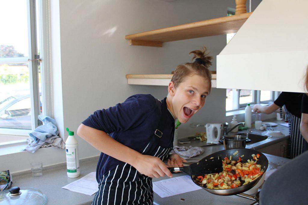 Glad kokkeelev i Gastronomi linjefaget står med pande og smiler
