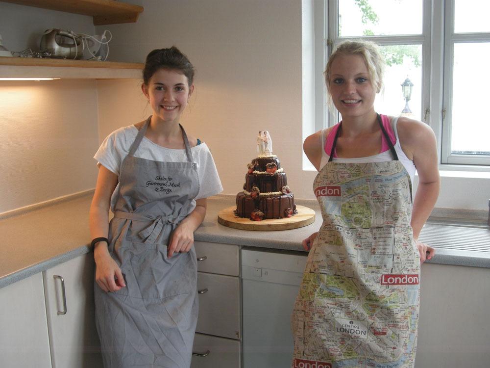 2 glade pige elever står i køkkenet med flot kage i baggrunden. Den har de selvfølgelig selv lavet.