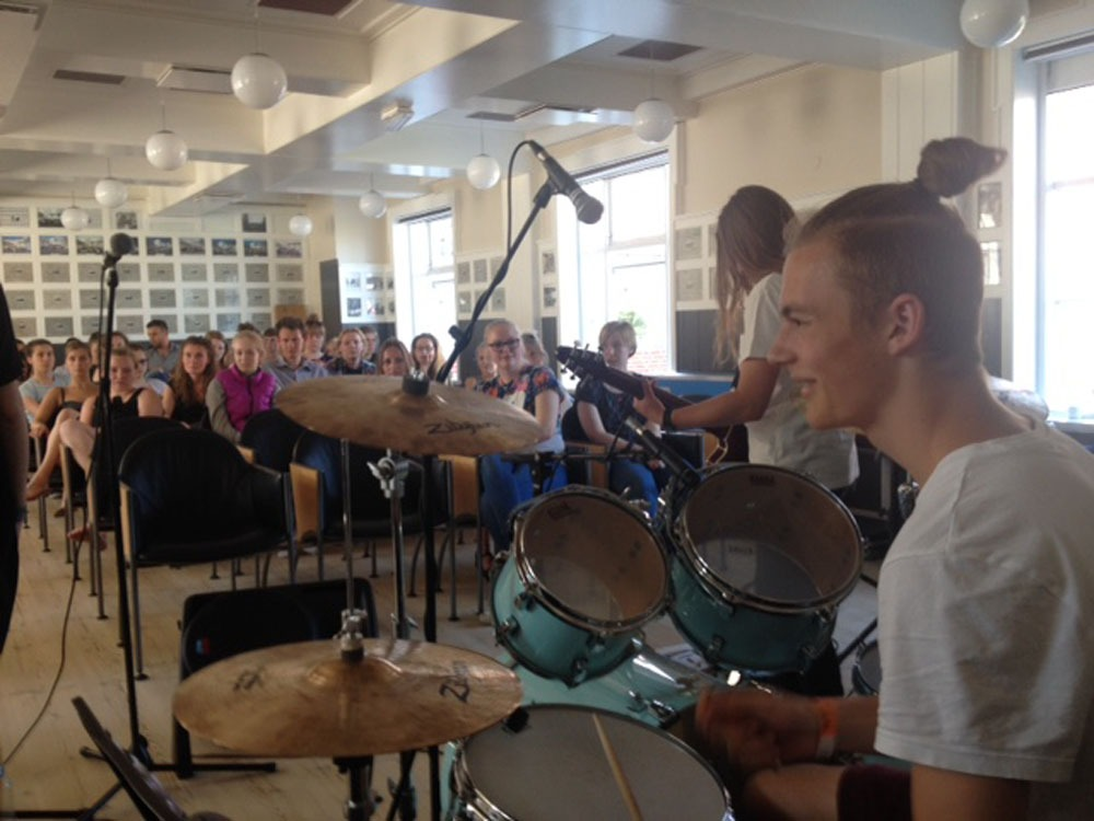 Dagligdagen med en elev der spiller på trommer, med alle elever og lærere siddende foran sig