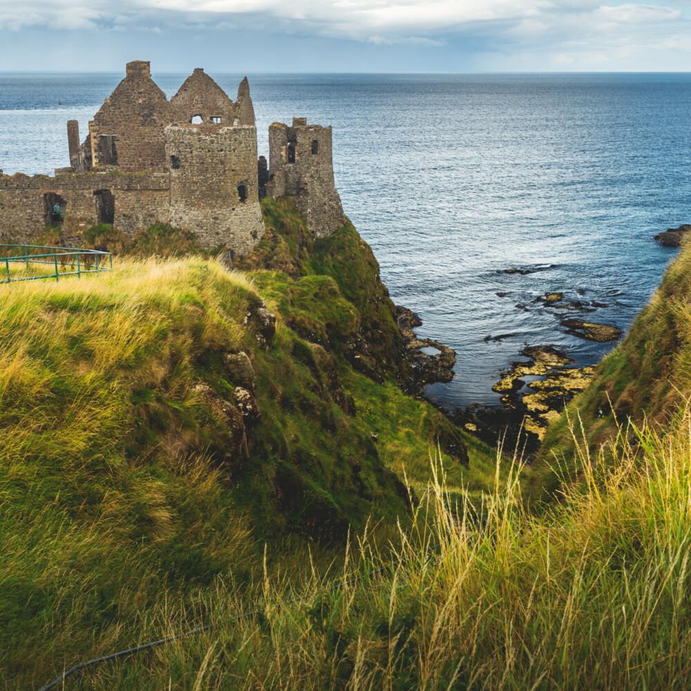 Dunluce castle on the cliff. Irish shoreline. Taxi Tours