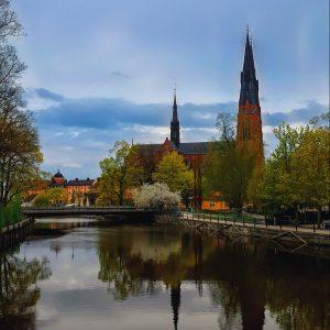 Foto på Uppsala domkyrka med Fyrisån i förgrunden