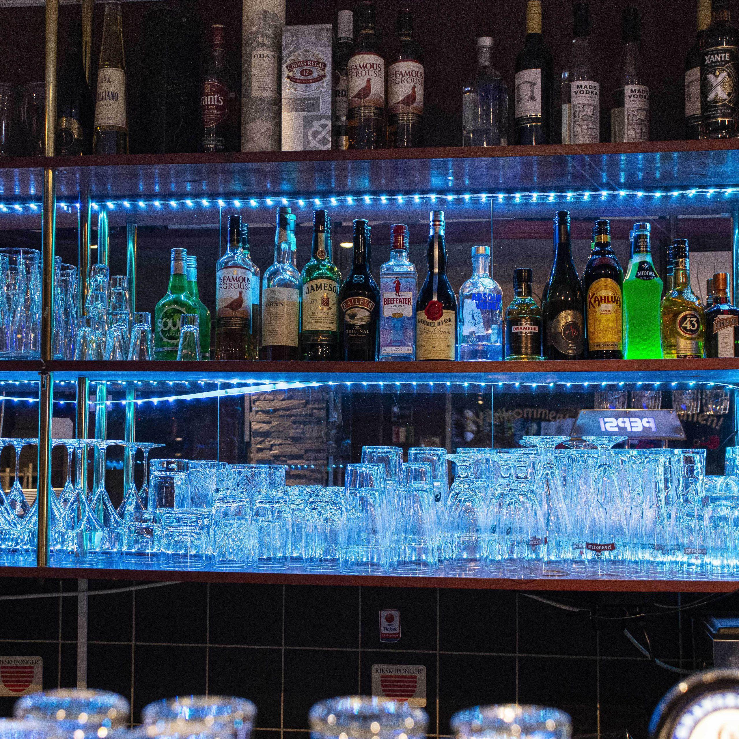 Vin och alkohol samt relevanta glas på hyllor med blått ljus