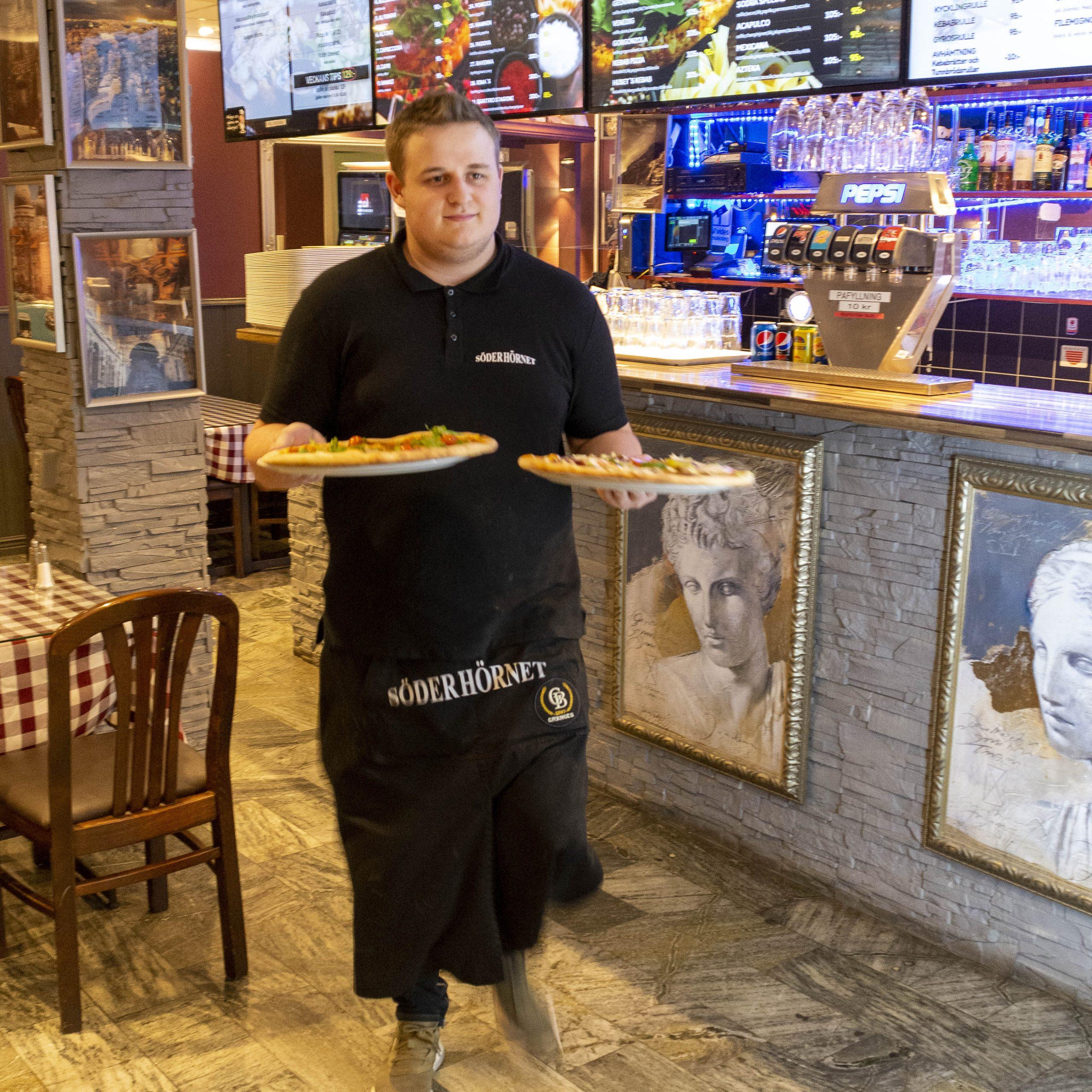 En servitör på väg att servera två pizzor