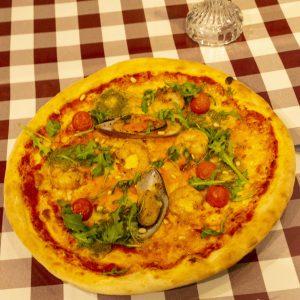 Pizza Gambera con Pesto - på ett bord, klar att ätas