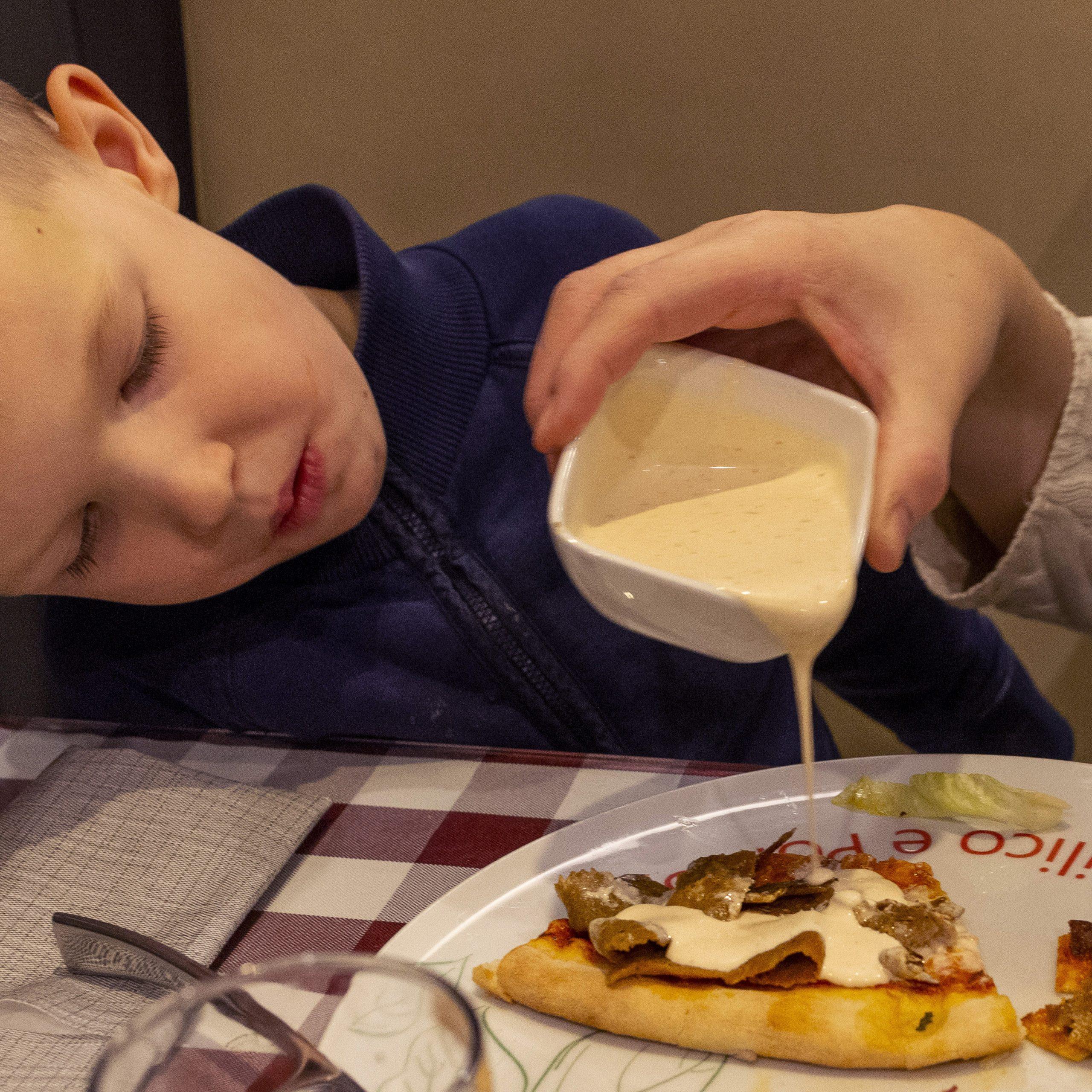 En ung pojke ser på när mamma häller kebabsås på hans pizza