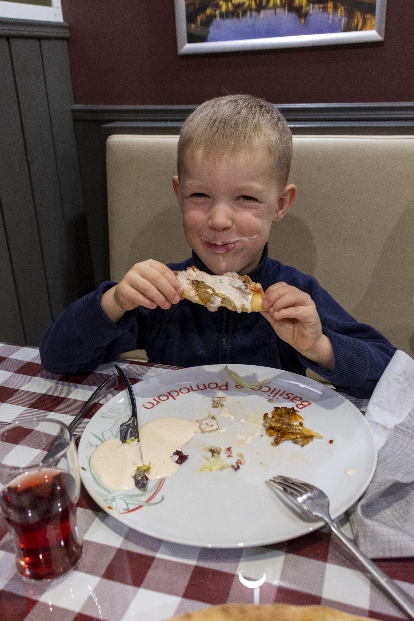 En glad pojke äter pizza med ett stort leende (och sås på ansiktet)