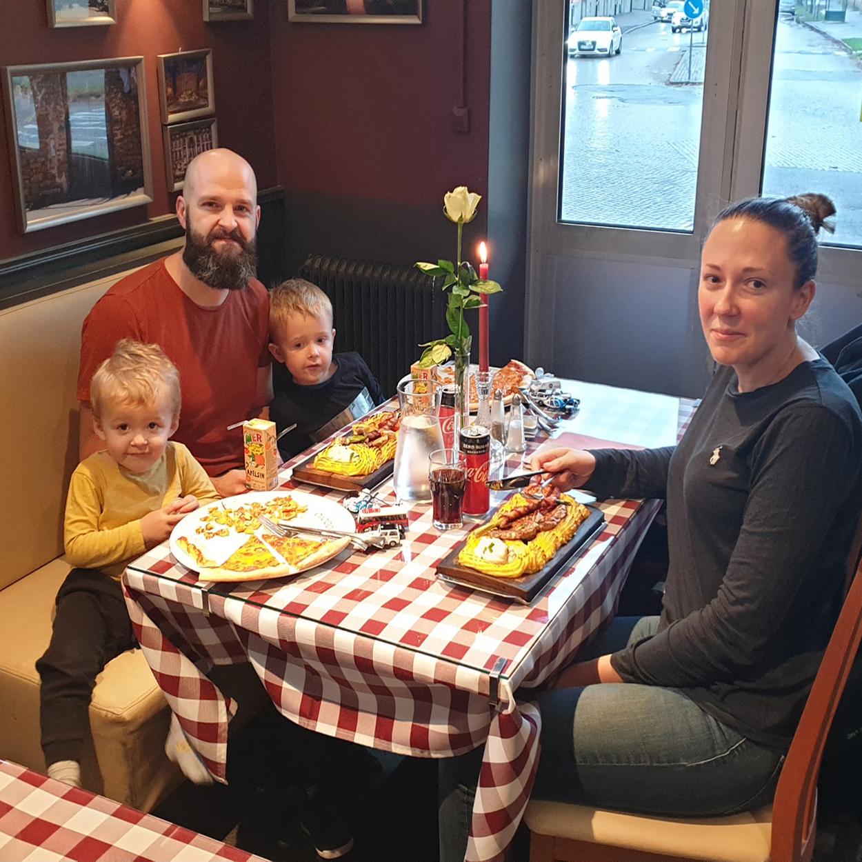 En familj med två små barn - plankstek och pizza, med blomma och tänt ljus