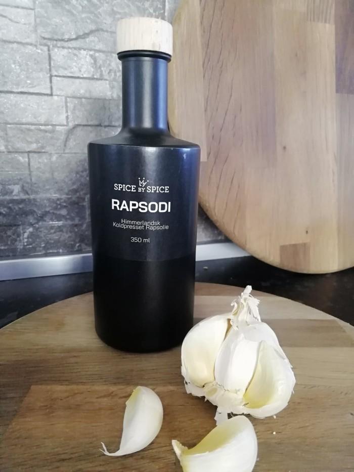 Himmerlandsk rapsolie i en sort glasflaske med råt trælåg. Placeret på et By Brorson pizabræt dekoreret med hvidløg. Nordisk design. Meget dekorativt på køkkenbord