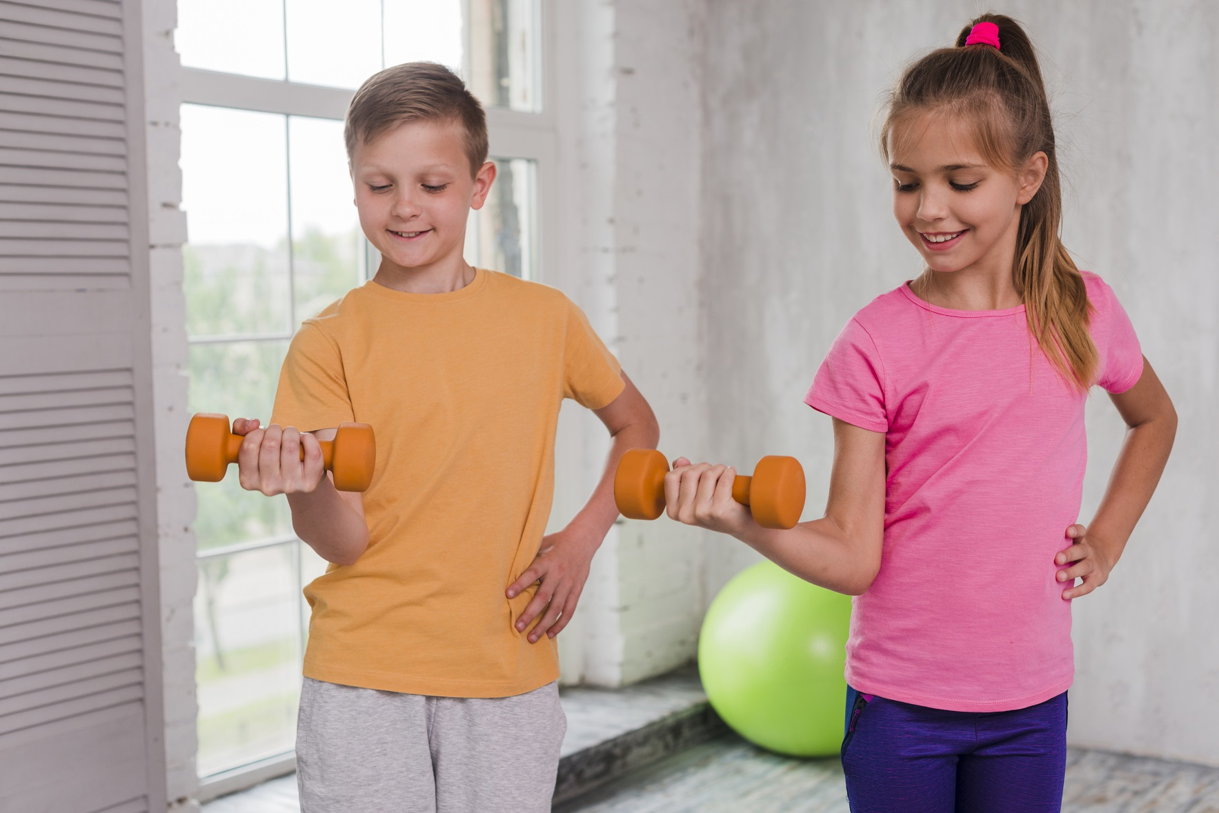 small-smiling-boy-girl-with-hand-hips-exercising-with-dumbbells