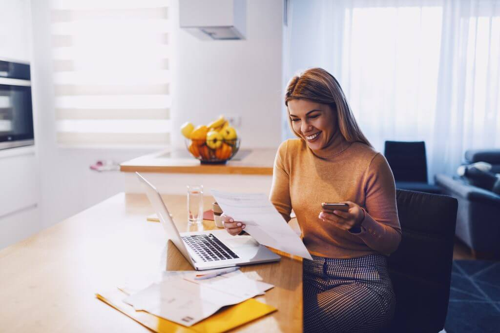 smiling woman in sweater holding paperwork in one hand and in other smart phone. On table are laptop and bills. Apartment interior.