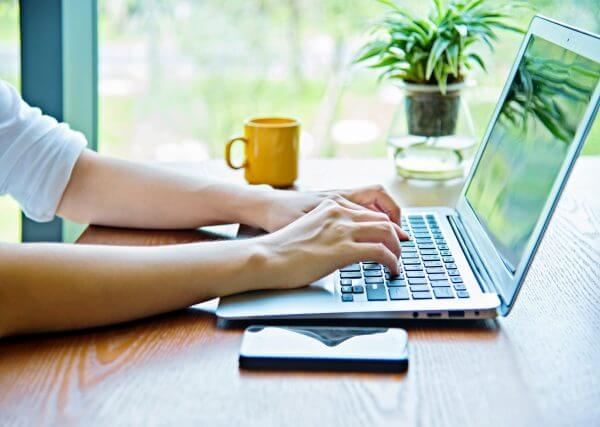 Woman hand typing on laptop