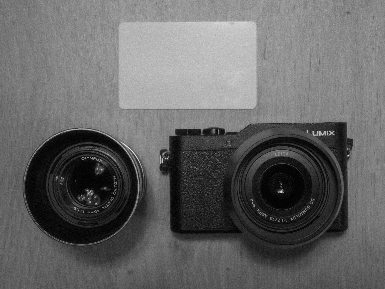 Panasonic GX800 next to a credit card and an Olympus 45mm lens