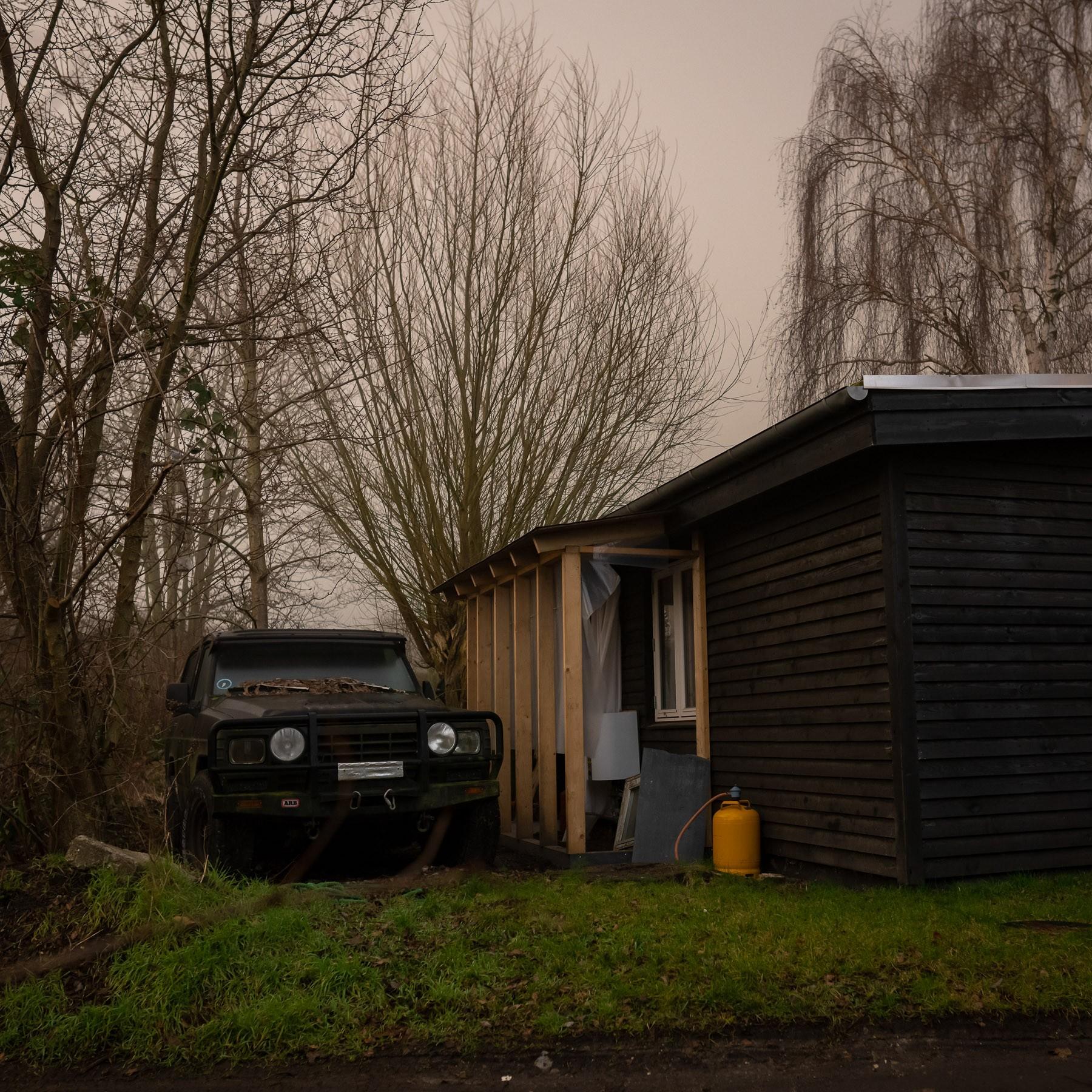 Hus under rekonstruktion samt gammel 4-hjulstrækker i indkørslen - Haveforeningen Nokken