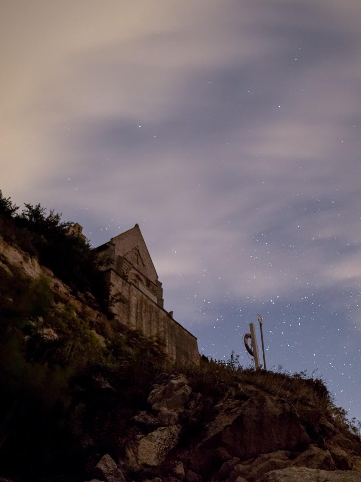 Højerup Kirke troner over Stevns Klint, der er skyer, men stjernene titter frem