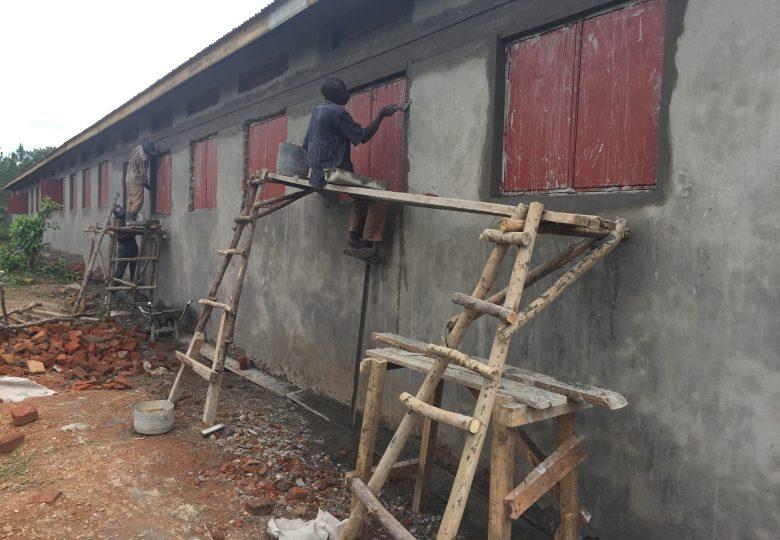 Man op houten steiger smeert de muren aan.
