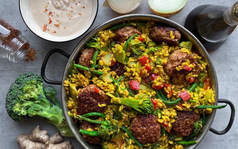 Havreris med curry och grönsaker, serverat med smakrika kycklingbullar och en sojasås