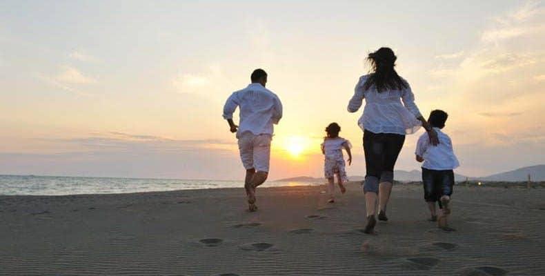 Billede af stressfri familie der løber på strand