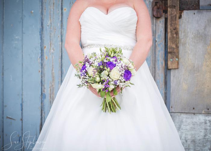 bride with purple and white boquet