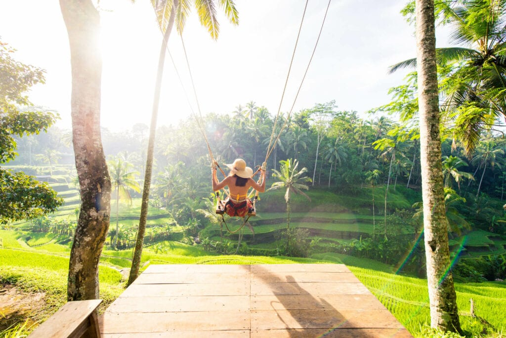 A girl at the popular Tegalalang Rice Terrace swing in Ubud at sunrise