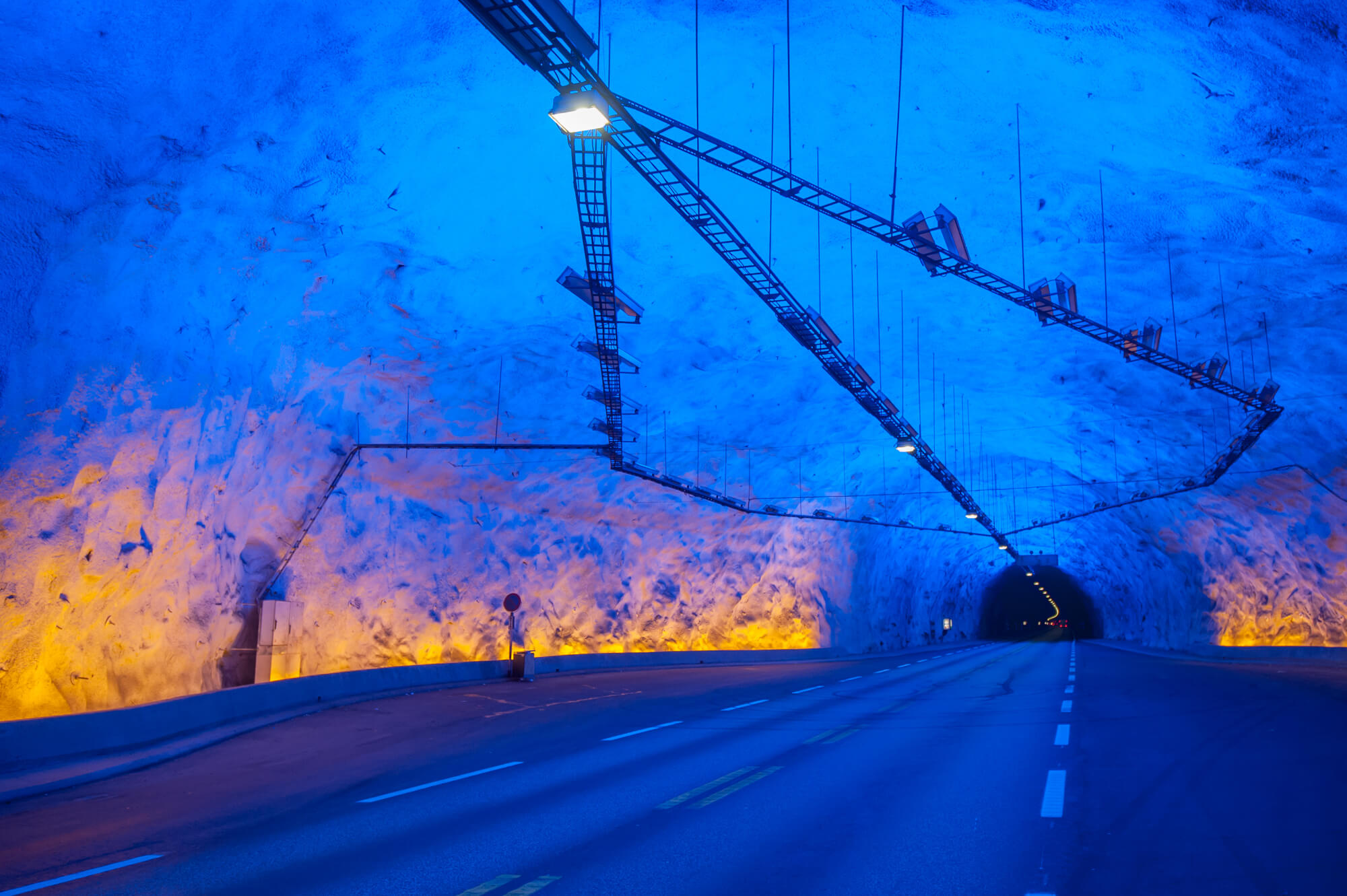Driving through a cave with yellow and blue lights in Lærdalstunnelen in western Norway