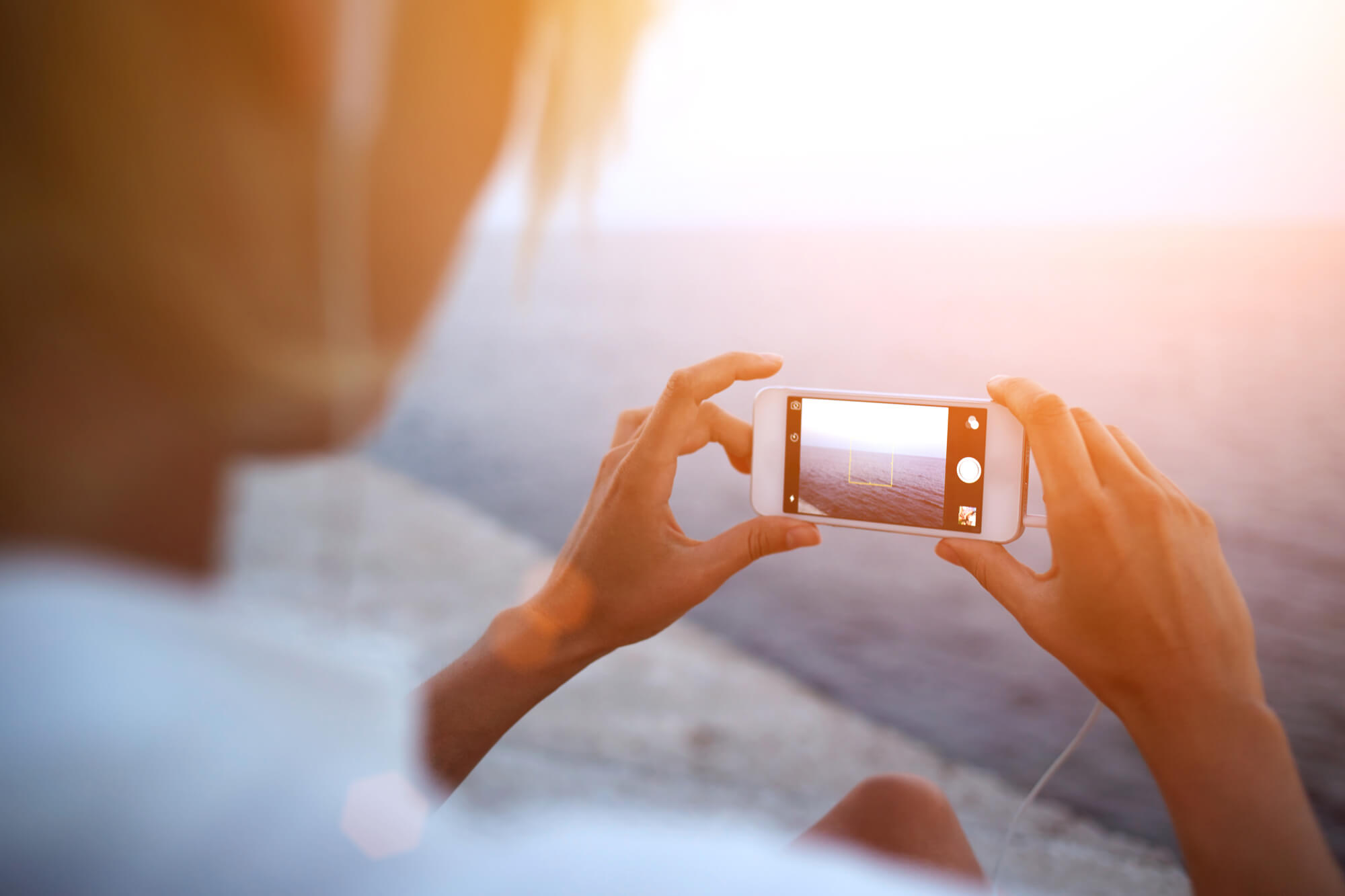 Woman taking photos on the beach for Instagram - 50+ Norway Instagram hashtags
