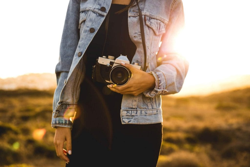 Best affordable camera for travel bloggers - Gurl holding camera at sunset