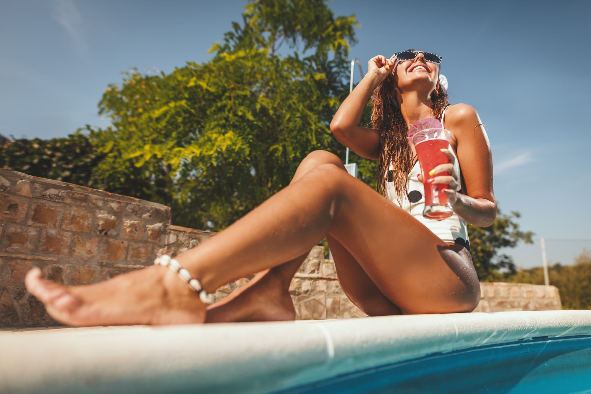 A smiling girl by the pool on a sunny day: Smile captions for Instagram