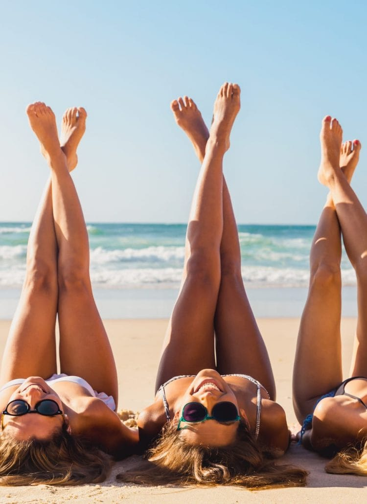 Three smiling girls, laying in the sand at the beach on a sunny day: Smile captions for Instagram