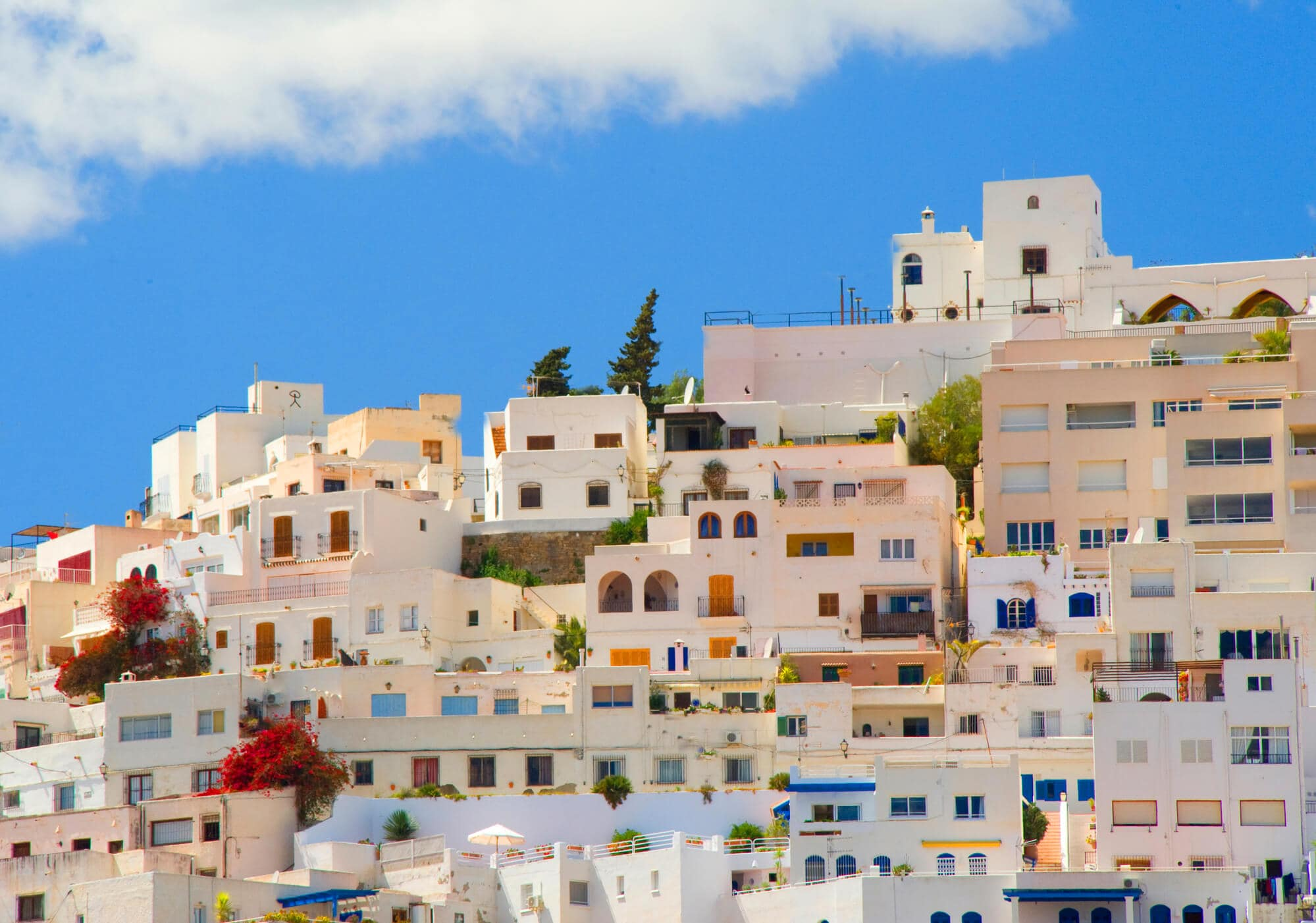 White houses with different colored doors on top of a hill in Mojácar Pueblo in Andalucía, Spain