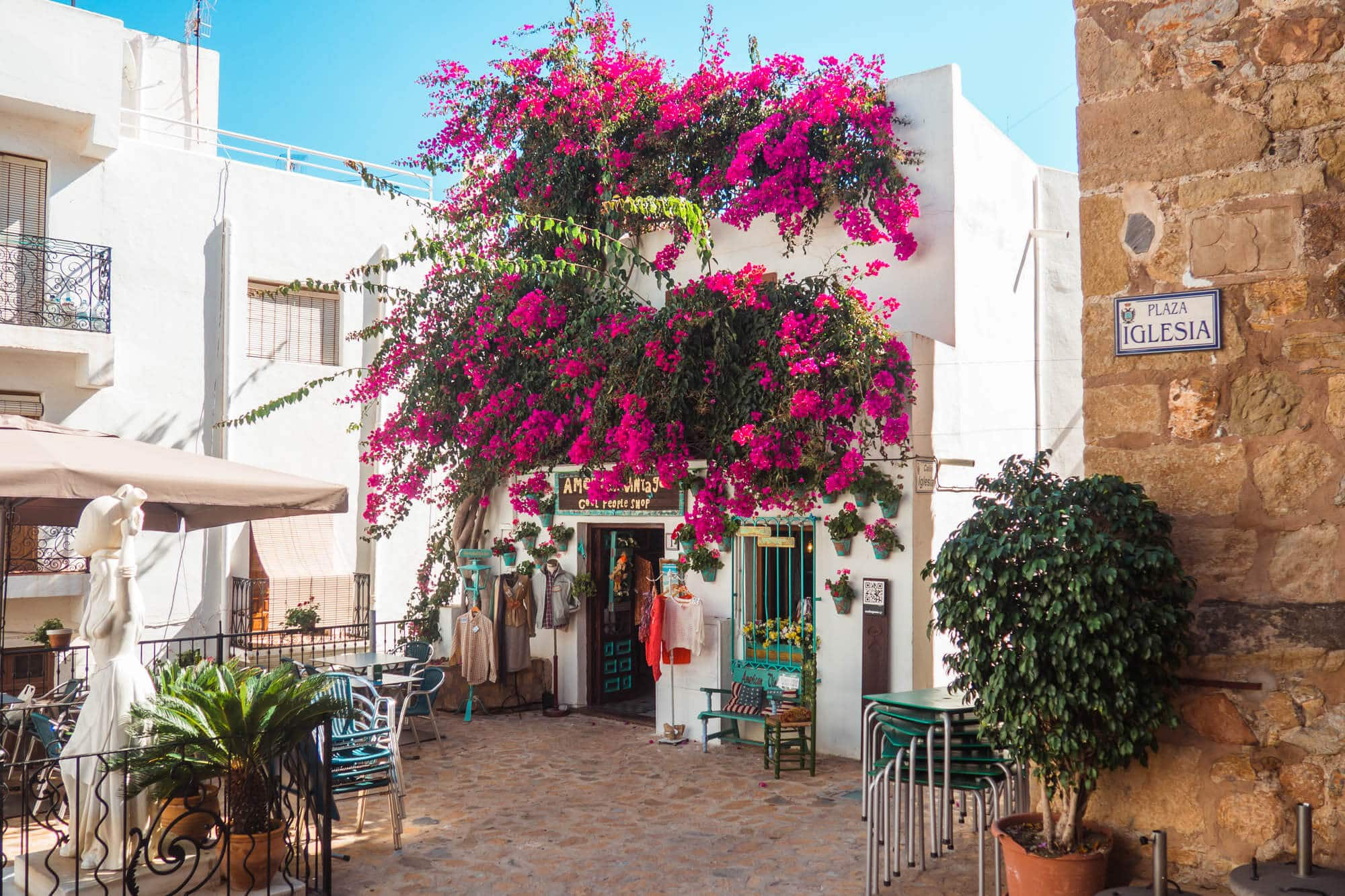 View of a beautiful white house covered in pink Bougainvillea and the Statue of Mojaquera in Plaza Iglesia in Mojacár Pueblo Spain