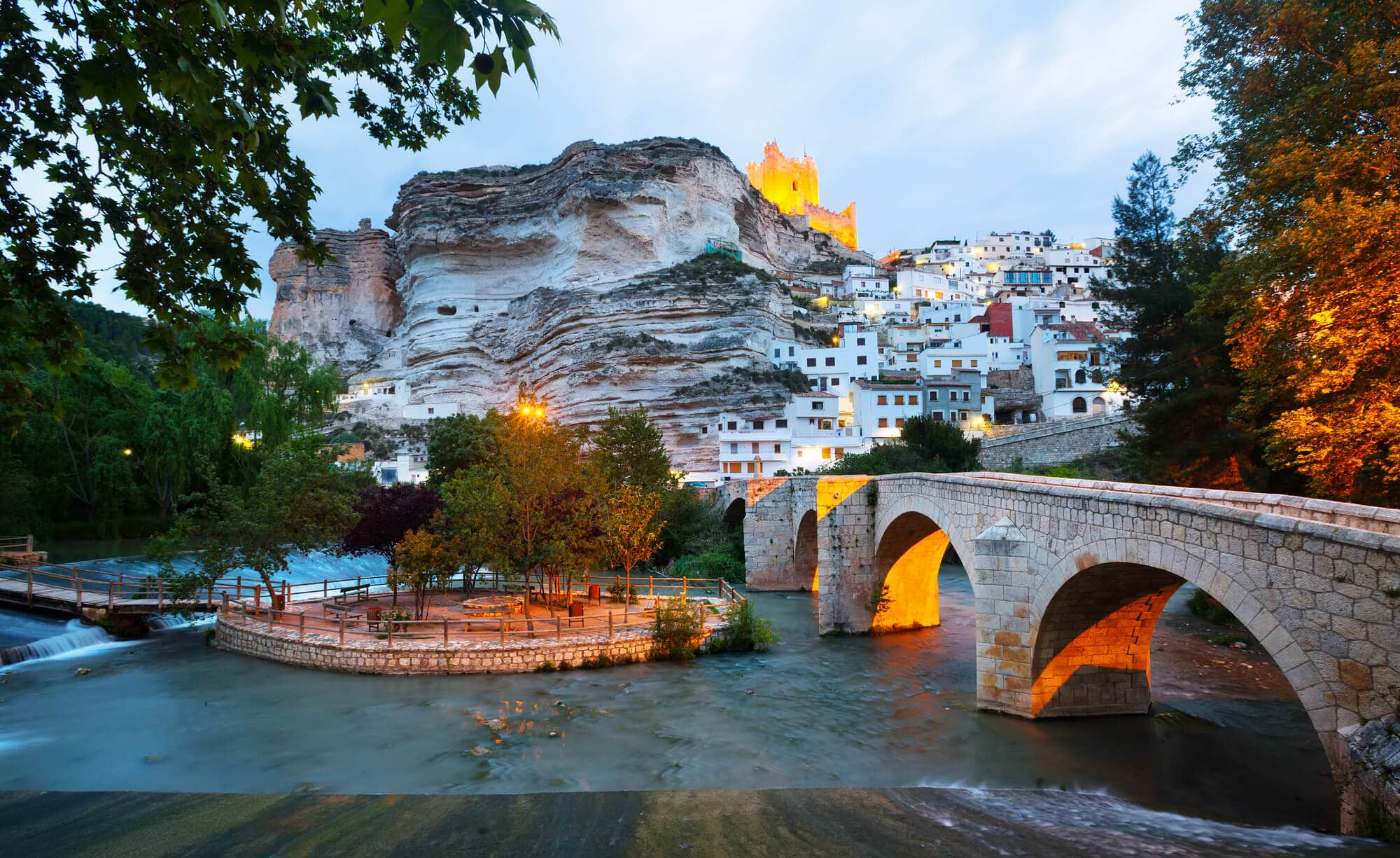 Evening view of a fortress on top of a large rock with white houses built into the rockface and a Roman bridge crossing the river in Alcalá del Júcar - A hidden gem in Spain that still feels like a secret