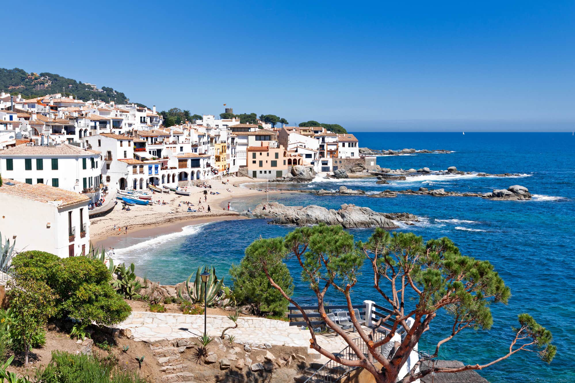 View of the beaches and white houses of Calella de Palafrugell on a sunny, clear day - One of the prettiest towns and hidden gem in Spain