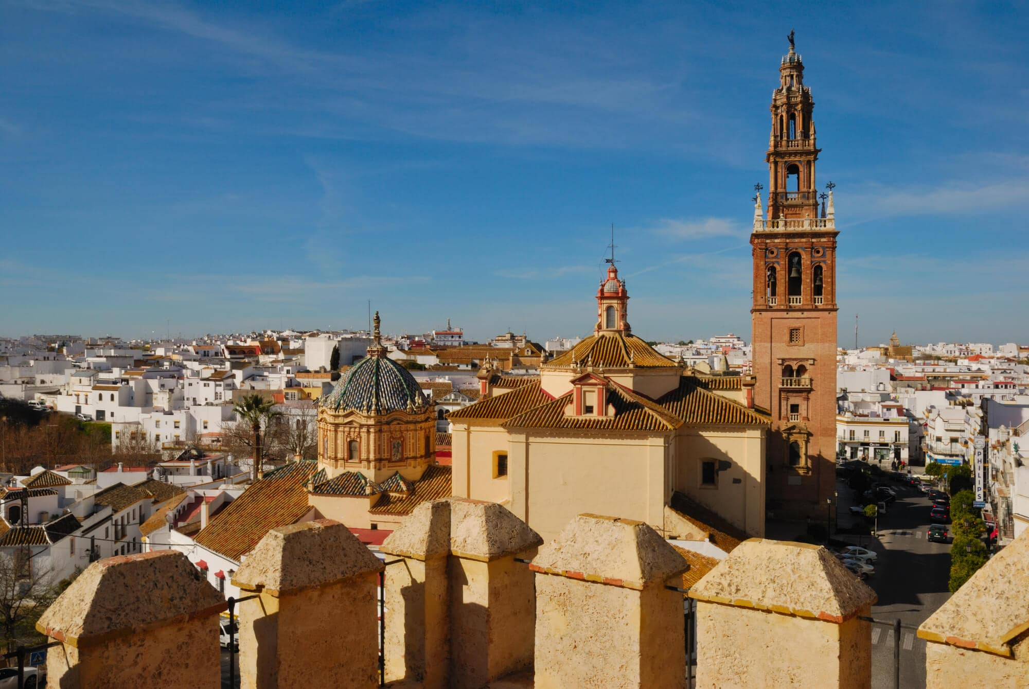 View from an old balcony over the white and golden rooftops in Carmona, Andalucía and a clear blue sky - A hidden gem and secret in Spain