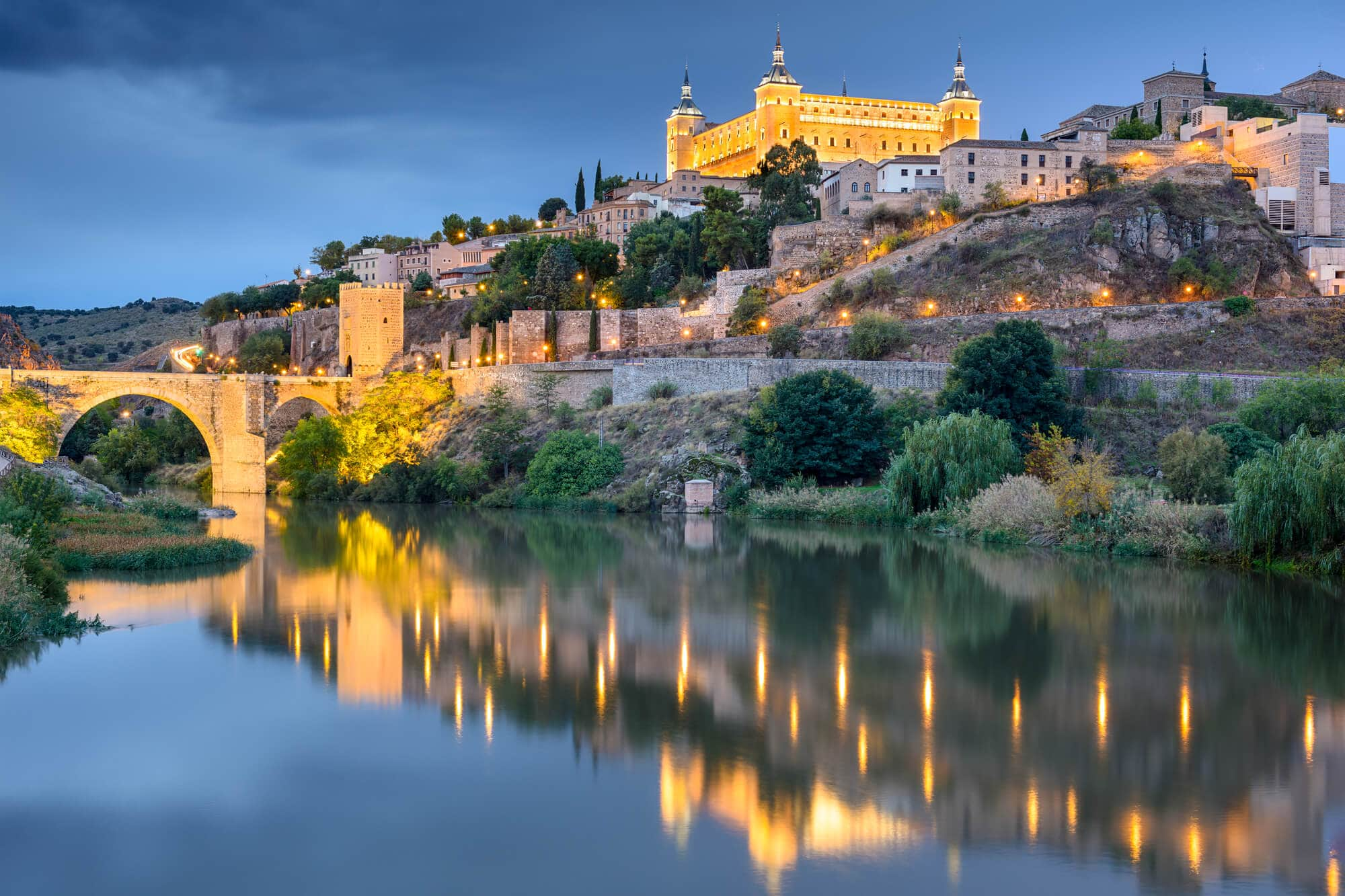 The beautiful Alcázar de Toledo lit up at dusk seen from the banks of the Tagus River - The Ultimate Spain Bucket List