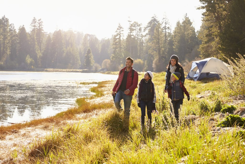 Parents and two children on camping trip walking near a lake