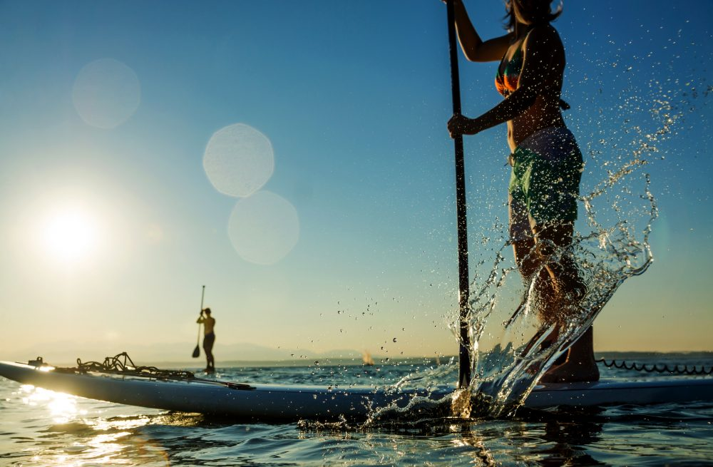 Woman paddling stand up paddle board splashing water.