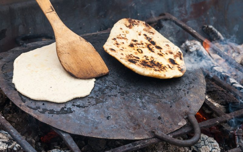 Two travel cakes bake on a roasting pan or baking tray on an open fire in accordance of the ancient Rome technology. A wooden spoon touches one of the cakes or scones.