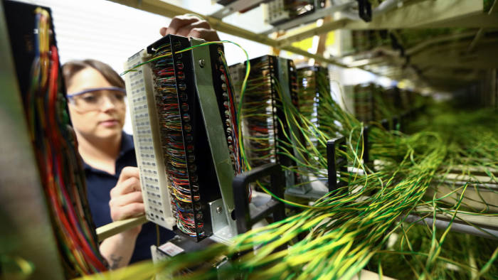 A network engineer from Openreach, a unit of BT Group Plc, works on copper jumper wires inside an exchange building in this arranged photograph in Upminster, U.K., on Thursday, Nov. 10, 2016. Regulator Ofcom called on BT, the U.K.'s former telecommunications monopoly, to set up a legally separate entity for the Openreach network unit within BT, with its own board, but stopped short of seeking a breakup. Photographer: Chris Ratcliffe/Bloomberg