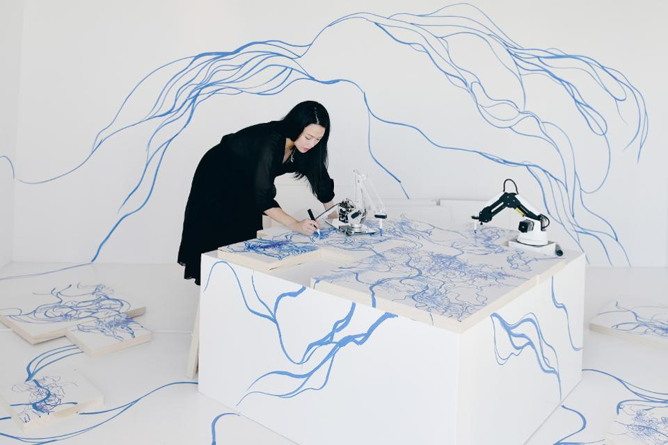Artist Sougwen Chung painting alongside two robotic arms in a white room