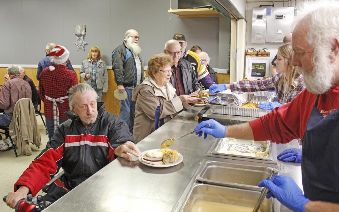 Volunteer Al Forseth, at right, serves a scoop of corn to David Hullinger during Wednesday's community Christmas meal at the American Legion in Park Rapids.