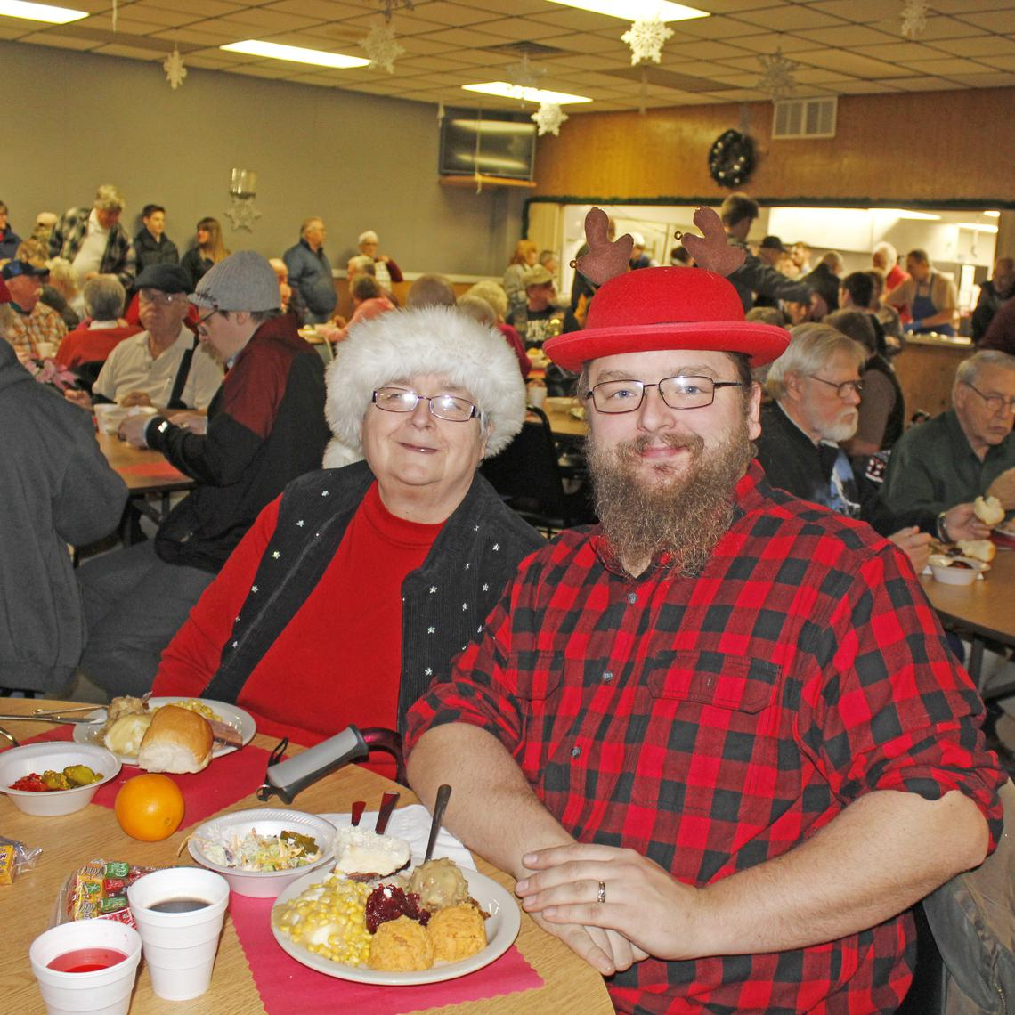 Linda Johnson and her son Derek Johnson attended the dinner in festive colors and Santa and reindeer hats.