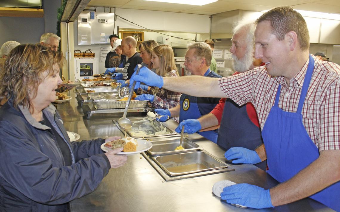 Volunteer Jerry Cook drizzles gravy on Marla Wolterstorff's mashed potatoes at the end of the serving line. Volunteers at the community meal fed more than 1,000 people on Christmas Day.