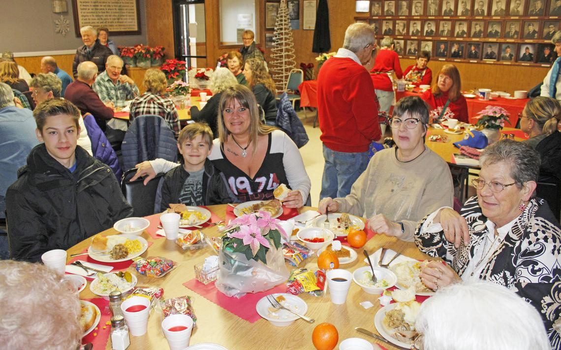 Chris and Wyatt Bruce, from left, and their mom Nancy Gruchow share a table at the community Christmas dinner with Laurine Kommer, Toni Becker and three other ladies.