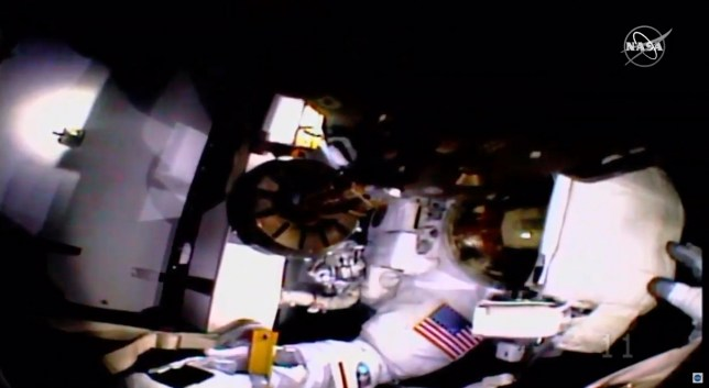 In this image taken from NASA video NASA astronaut Jessica Meir, hand seen at right, holds the helmet of fellow astronaut Christina Koch in place as they work to finish upgrades to the International Space Station's power grid, Wednesday, Jan. 15, 2020. The women were barely a half-hour into their latest spacewalk when Koch's helmet camera and lights came loose. Meir tried to get the camera and light attachment back onto Koch's helmet, but could not get it into the proper grooves. It was the second pairing of Meir and Koch outside the orbiting lab. (NASA via AP)