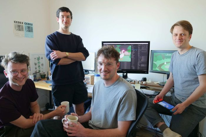 The four game creators pose for a photo in their studio