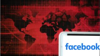 The logo of social media giant Facebook is seen on a screen of a phone next to a red illustration of world and financial markets.