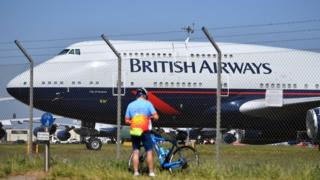 A cyclist standing near a British Airways plane