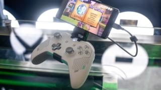 An Xbox controller is seen with a phone clipped to its top