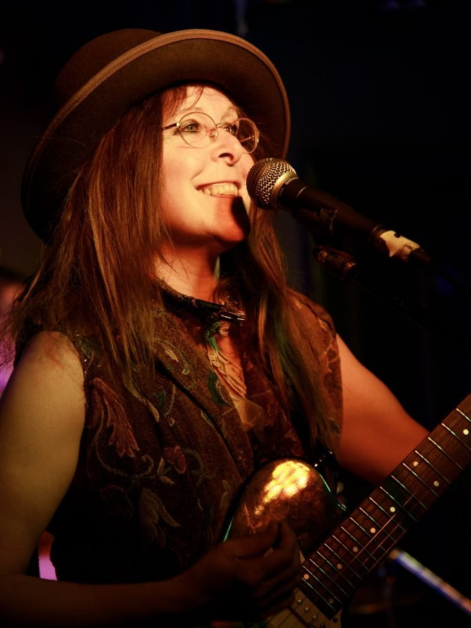 Woman in glasses and hat at microphone with electric guitar