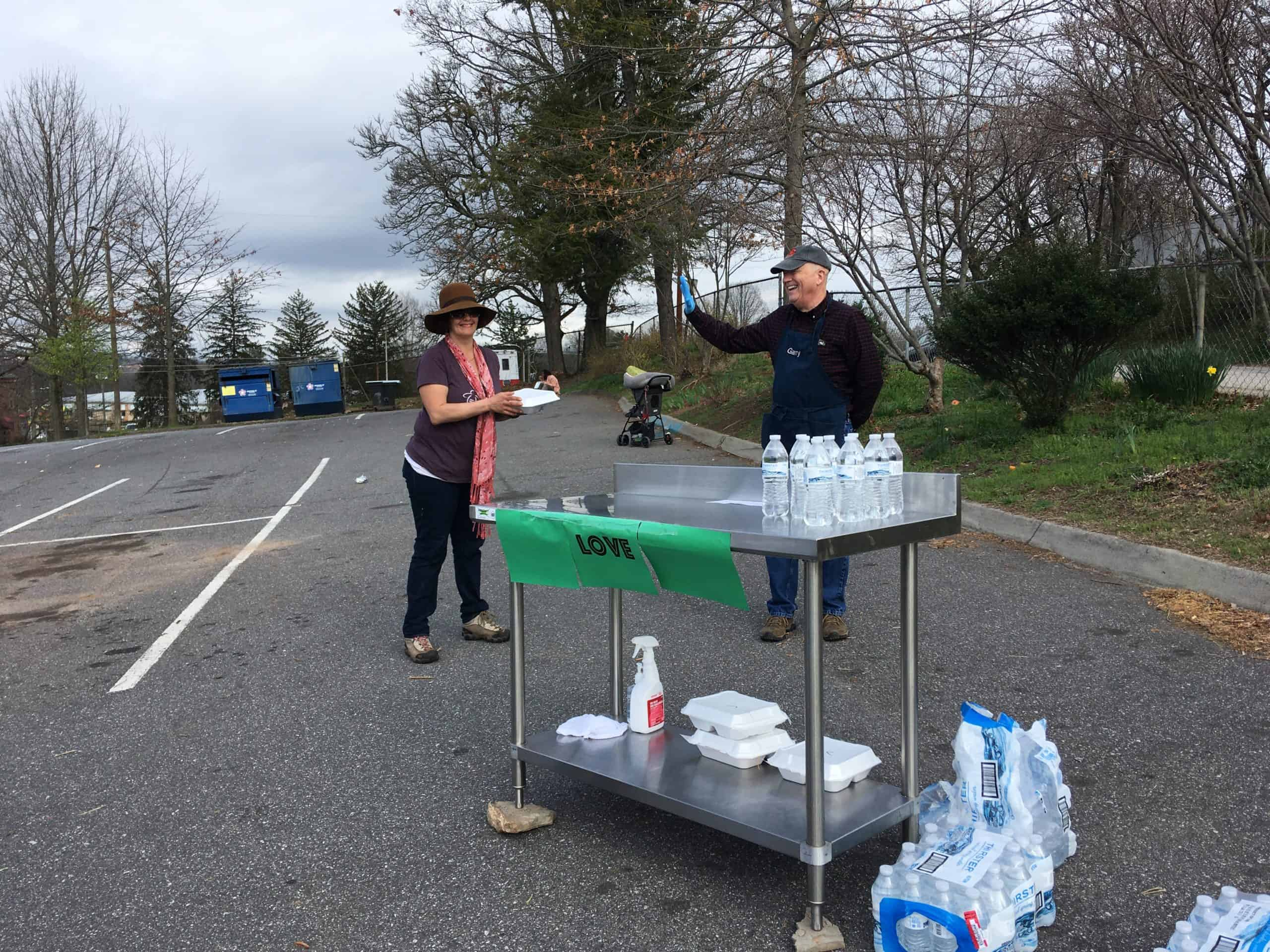 Volunteers at a water bottle station stand far apart at a parking lot to help with coronavirus social distancing while still serving meals to the homeless.